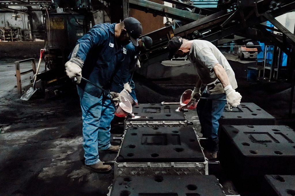 Pouring molten aluminum into sand cast mold